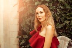 Een mooie jonge vrouw in een asymmetrische rood-Bourgondië cocktailkleding op één schouder zit in een restaurant en gelukkig glim stock afbeelding