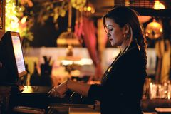 Een mooie jonge vrouw bij het bureau in een restaurant stock afbeeldingen