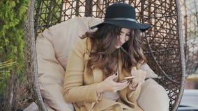 Een mooie jonge vrouw die een laag en een zwarte hoed op haar hoofd dragen zit als voorzitter in een koffie en typt sms in stock footage