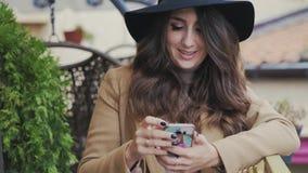 Een mooie jonge vrouw die een laag en een zwarte hoed op haar hoofd dragen zit als voorzitter in een koffie en typt sms in stock videobeelden