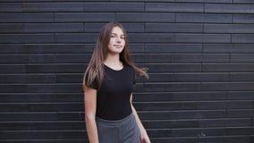Een mooie jonge vrouw die met bruin haar op een winderige dag langzame motie glimlachen royalty-vrije stock afbeeldingen