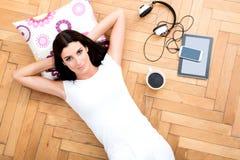 Een mooie jonge vrouw die op de vloer, met elektronische gad leggen royalty-vrije stock fotografie
