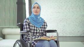 Een mooie jonge vrouw in een hijab is blind of zwak opleggend, een rolstoel lezend een braille-doopvont stock videobeelden