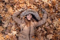Een mooie jonge vrouw ligt op de bladeren, genietend van de herfst stock foto's