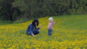 Een mooie, jonge vrouw met een kind loopt in een stadspark De moeder en de dochter lopen rond het gebied met stock footage