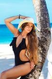 Een mooie jonge vrouw met lang haar in een strohoed ontspant  Stock Foto's
