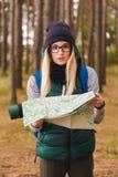 Een mooie jonge vrouw met reiskaart en rugzak in pijnboomaanplantingen royalty-vrije stock fotografie
