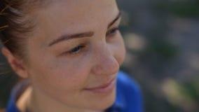 Een mooie jonge vrouw met rood haar in een denimkleding en sproeten op haar gezicht zit in het Park op een bank op a stock video