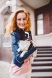 Een mooie jonge vrouw met rood lang haar houdt een kleine, leuke grappige groot-eyed hond van twee bloemen, een zwart-wit huisdie stock foto