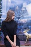 Een mooie jonge vrouw in trui op achtergrond van Kerstmislichten royalty-vrije stock foto