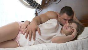 Een mooie jonge zwangere vrouw en haar spierechtgenoot liggen op het bed, strijkt de echtgenoot de buik van zijn vrouw stock video