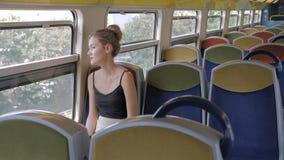 Een mooie Kaukasische vrouwelijke toerist berijdt alleen in een lege cabinemetro en kijkt uit het venster Achter haar zijn stock videobeelden