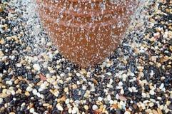 Een mooie kleine fontein in de vorm van een bruine vaas, een kruik met dalende dalingen van water bij de gekleurde stenen status royalty-vrije stock fotografie