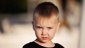 Een mooie kleine jongen bekijkt de camera De zon glanst stock foto's