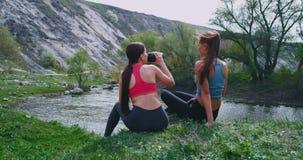 In een mooie landschapsmening bij aard twee hebben de dames met het praktizeren sport een dorstige onderbrekingstijd drinkend wat stock footage