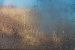 Een mooie mening van de de herfststad door nat misted glas stock afbeelding