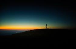 Een mooie mening van de zonsondergang in bergen met een verkeerstekenpost Stock Foto's