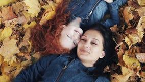 Een mooie moeder en haar leuke dochter liggen op een geel blad in het de herfstpark Zij die de camera, hoogste mening onderzoeken stock videobeelden