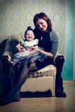 Een mooie moeder steunt een klein kind in haar kleding en hoed royalty-vrije stock afbeeldingen