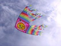 Een mooie multicolored vlieger stijgt in de blauwe hemel royalty-vrije stock foto