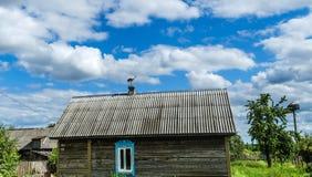 Een mooie ooievaarsvogel met een rode bek zit op een schoorsteen van een blokhuis in een dorp tegen royalty-vrije stock afbeeldingen