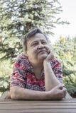 Een mooie oude vrouwenzitting bij tuin royalty-vrije stock fotografie