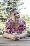Een mooie oude vrouwenzitting en het spreken bij tuin royalty-vrije stock afbeelding