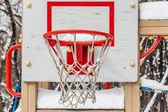 Een mooie rode basketbalhoepel met witte kabel netto en witte sneeuw op de speelplaats van de kinderen in de yard in de winter royalty-vrije stock afbeeldingen