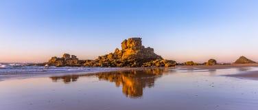 Een Mooie rotsbezinning bij het strand in Algarve Stock Afbeelding