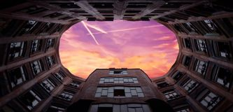 Een mooie roze en rode zonsondergang in het kader van één van meest verbazende gebouwen van Antonio Gaudà de Stock Foto's