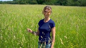 Een mooie slanke vrouw bevindt zich en glimlacht in de weide, vingertechniek de aartjes van vers gras op een duidelijke Zonnige d stock videobeelden