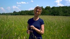 Een mooie slanke vrouw bevindt zich en glimlacht in de weide, vingertechniek de aartjes van vers gras op een duidelijke zonnige d stock footage