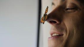 Een mooie vlinder zit op de neus van een jonge mens de kerel glimlacht en de vlinder klapt zijn vleugels stock videobeelden