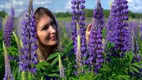 Een mooie vrouw, bewondert de purpere bloemen in de weide op een Zonnige dag en glimlacht Gezicht en bloemenclose-up stock video