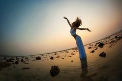 Een mooie vrouw die op het strand dansen Stock Fotografie