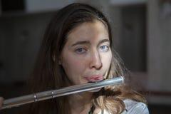 Een mooie vrouw die terwijl het spelen op een fluit stellen royalty-vrije stock foto's