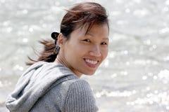 Een mooie vrouw door het water. Stock Afbeelding