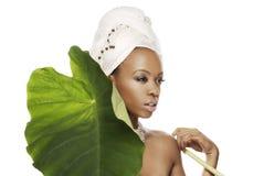 Een mooie vrouw en een groot groen blad royalty-vrije stock afbeeldingen