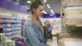 Een mooie vrouw kiest hoofdkussens of deken in een supermarkt Bepaald met een keus Neem het verpakkende product van stock videobeelden