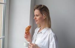 Een mooie vrouw kijkt uit het venster De koffie van de drankochtend met croissant stock afbeelding