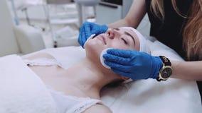 Een mooie vrouw met gesloten ogen, die op cosmetologist's liggen dient in, de dermatoloog gebruikend katoenen sponsen aan stock videobeelden