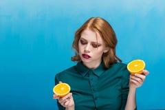 Een mooie vrouw met een heldere samenstelling en een goed-verzorgde gezichtshuid houdt een sinaasappel op haar hand royalty-vrije stock foto's