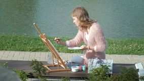 Een mooie vrouw met rood haar, schildert een beeld op canvas, dat zich op de schildersezel bevindt De dame is in openlucht dichtb stock video