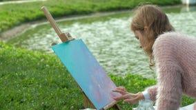 Een mooie vrouw met rood haar, schildert een beeld op canvas, dat zich op de schildersezel bevindt De dame is in openlucht dichtb stock videobeelden