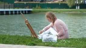 Een mooie vrouw met rood haar, schildert een beeld op canvas, dat zich op de schildersezel bevindt De dame is in openlucht dichtb stock footage