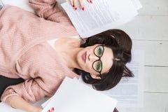 Een mooie vrouw in modieuze glazen ligt op de vloer onder de documenten en de documenten, de meisjes freelancer glimlachen en royalty-vrije stock afbeeldingen