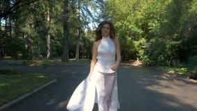 Een mooie vrouw in een wit kostuum loopt snel en loopt in het stadspark stock video