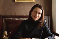 Een mooie vrouw zit bij een lijst in een koffie royalty-vrije stock afbeeldingen