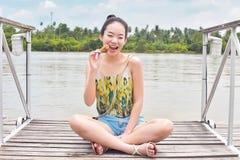 Een mooie vrouw zit naast rivier royalty-vrije stock afbeelding
