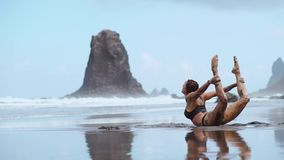Een mooie vrouw in een zwempak voert een oefeningsbrug op het strand met zwart vulkanisch langs omringd zand uit stock video